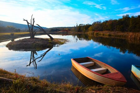 Tranquil scene of a small red and white fishing boat on a small rural pond at sunset with blue sky and autumn foliage reflecting in the calm water Stock Photo - 17347508