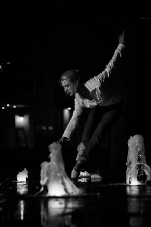 Young adult blonde ballerina dancing at night under signs and lamp posts in a general urban area  Shallow Depth of Field and in black and white photo