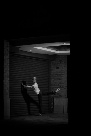 Young adult blonde ballerina dancing at night under signs and lamp posts in a general urban area Stock Photo - 17343311