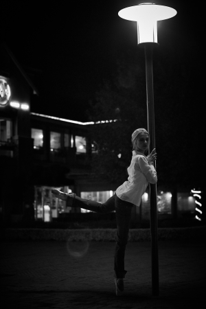 Young adult blonde ballerina dancing at night under signs and lamp posts in a general urban area  Shallow Depth of Field and in black and white  Textured and Grungy photo