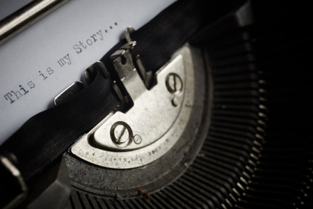 A Closeup image of the typebars and ribbon of an old style typewriter and paper with the text  My Story     Shallow Depth of Field  in a panorama crop photo