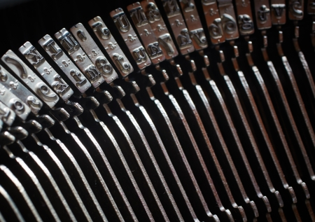 A Closeup image of the inverted keys or typebars of an old style typewriter in monotone  Shallow Depth of Field  photo