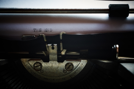 A Closeup image of the typebars and ribbon of an old style typewriter and paper with the text  THE END  Shallow Depth of Field Stock Photo - 17385452