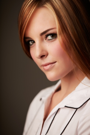 Beautiful young caucasian adult woman with long auburn red hair on a plain background, wearing a white button shirt  Stock Photo - 17364503