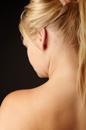 Nude Young adult caucasian woman holding her blonde hair up with one hand against a dark background and seen from behind   photo