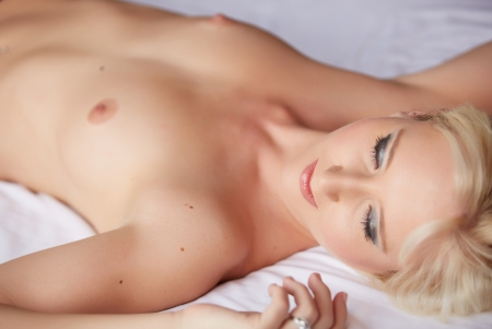 naked woman breasts: Beautiful and very sexy young adult caucasian woman in Black lingerie with blonde hair and blue eyes, in a bedroom setting with typical boudoir poses