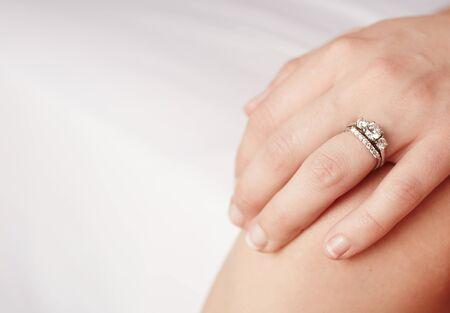 anillo de compromiso: La mano de una mujer adulta de raza blanca con un anillo de compromiso de diamantes en su dedo anular izquierdo