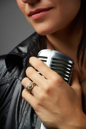 Young adult caucasian female singer with red lips and wearing a black leather jacket holding an old style microphone in her left hand - closeup Stock Photo - 18394537