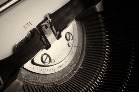 A Closeup image of the typebars and ribbon of an old style typewriter and paper with the letters: NB! (Shallow Depth of Field) Stock Photo - 18406568