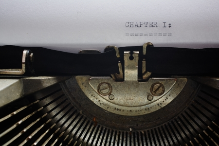 A Closeup image of the typebars and ribbon of an old style typewriter and paper with the text: CHAPTER 1: (Shallow Depth of Field) Stock Photo - 18406572
