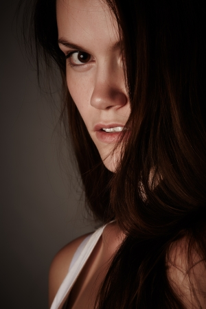 high contrast: Portrait of a beautiful and tall young adult caucasian woman with long brown hair, on a grey background with a serious facial expression.