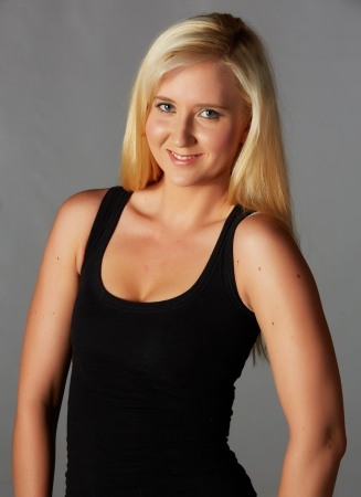 Beautiful and very sexy young adult caucasian woman in a casual black top with blonde hair and blue eyes, against a grey background Stock Photo - 18394534