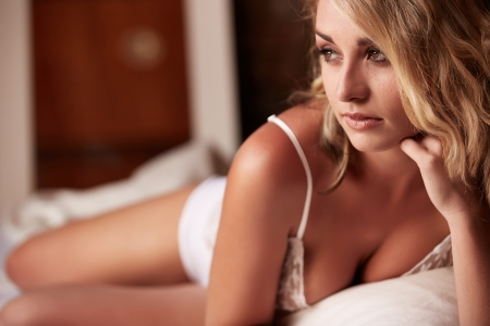 Extremely beautiful and sexy young adult caucasian woman with honey blonde hair wearing lingerie in a boudoir bedroom setting in various poses Stock Photo - 18518183