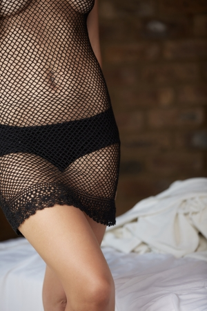 Extremely beautiful and sexy young adult caucasian woman with honey blonde hair wearing fishnet lingerie in a boudoir bedroom setting in various poses Stock Photo - 18518208