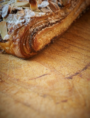 Fresh chocolate and Almond rollover croissant pastry, sprinkled with icing sugar on a brown wooden serving board with copy space  - Shallow Depth of Field  DOF Stock Photo - 18518169