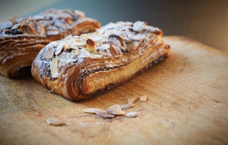 Fresh chocolate and Almond rollover croissant pastry, sprinkled with icing sugar on a brown wooden serving board with copy space  - Shallow Depth of Field  DOF  Stock Photo - 18518178