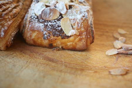 Fresh chocolate and Almond rollover croissant pastry, sprinkled with icing sugar on a brown wooden serving board with copy space  - Shallow Depth of Field  DOF  Stock Photo - 18518206