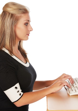 Beautiful and sexy young adult caucasian businesswoman with honey blonde hair wearing a casual business outfit working on a computer with her hands on a keyboard Stock Photo - 18659679