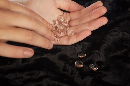 fake diamond: A woman with fake diamonds in her hand counting them out on a black velvet tabletop