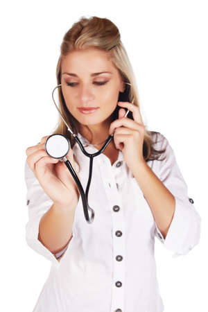 Beautiful young adult caucasian medical doctor with honey blonde hair wearing a casual white outfit and with a stethoscope in her hands against a white background - Shallow DOF, Focus on Stethoscope and hand  Stock Photo - 18659636