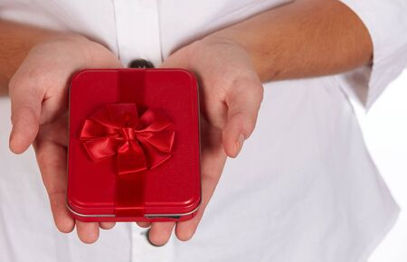 Female caucasian hands holding a red gift box with a red ribbon and bow Stock Photo - 18706260