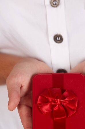 Female caucasian hands holding a red gift box with a red ribbon and bow Stock Photo - 18706259