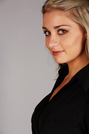 honey blonde: Beautiful and sexy young adult caucasian businesswoman with honey blonde hair wearing a casual black business outfit against a grey background