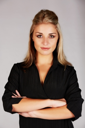 honey blonde: Beautiful and sexy young adult caucasian businesswoman with honey blonde hair wearing a casual black business outfit against a grey background and with her arms crossed Stock Photo
