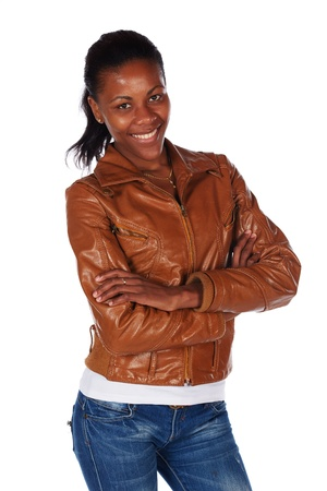 slicked back hair: Beautiful black african young adult woman casually dressed in a brown leather jacket and Blue jeans with her hair slicked back into a ponytail and isolated on a white background Stock Photo