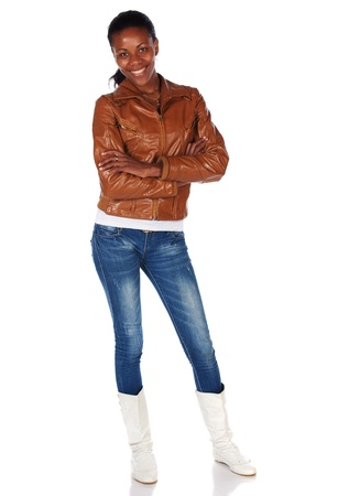 slicked: Beautiful black african young adult woman casually dressed in a brown leather jacket and Blue jeans with white boots and with her hair slicked back into a ponytail and isolated on a white background