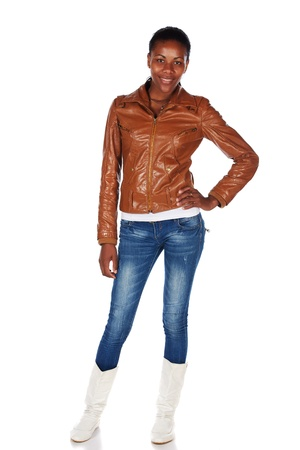 slicked: Beautiful black african young adult woman casually dressed in a brown leather jacket and Blue jeans with white boots and with her hair slicked back into a ponytail and isolated on a white background - hands on hips Stock Photo