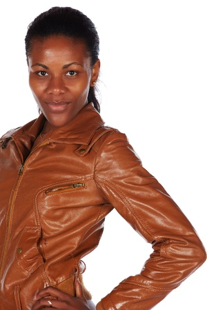 slicked back hair: Beautiful black african young adult woman casually dressed in a brown leather jacket with her hair slicked back into a ponytail and isolated on a white background Stock Photo