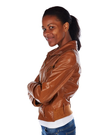 slicked back hair: Beautiful black african young adult woman casually dressed in a brown leather jacket and Blue jeans with her hair slicked back into a ponytail and isolated on a white background - arms crossed