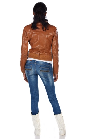 Beautiful black african young adult woman casually dressed in a brown leather jacket and Blue jeans with white boots and with her hair slicked back into a ponytail and isolated on a white background Stock Photo - 19371659