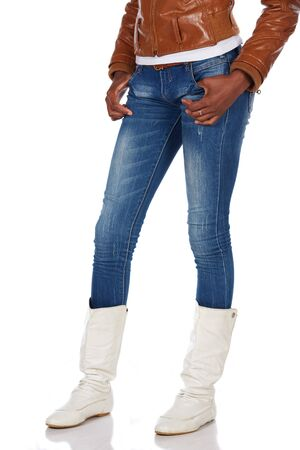 Beautiful black african young adult woman casually dressed in a brown leather jacket and Blue jeans with white boots and isolated on a white background Stock Photo - 19372817