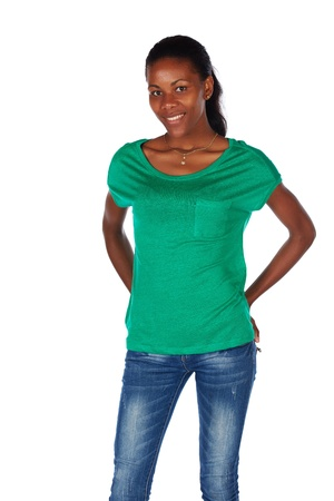 slicked back hair: Beautiful black african young adult woman casually dressed in an emerald green t-shirt and Blue jeans and with her hair slicked back into a ponytail and isolated on a white background