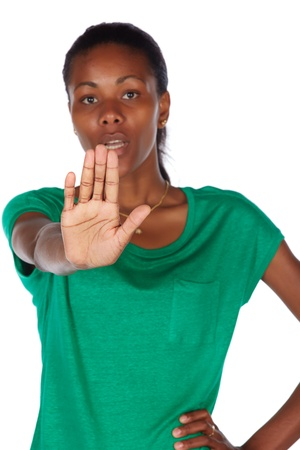 slicked: Pretty black african young adult woman casually dressed in an emerald green t-shirt with her hair slicked back into a ponytail and isolated on a white background - upset and angry with her hand in a stop gesture  Stock Photo