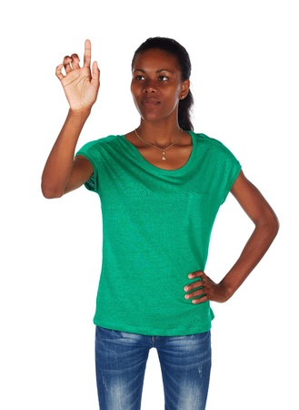 slicked back hair: Beautiful black african young adult woman casually dressed in an emerald green t-shirt and Blue jeans and with her hair slicked back into a ponytail and isolated on a white background and with her hand in the air, touching or pointing at something