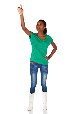 slicked back hair: Beautiful black african young adult woman casually dressed in an emerald green t-shirt and Blue jeans with white boots and with her hair slicked back into a ponytail and isolated on a white background and with her hand in the air, touching or pointing at