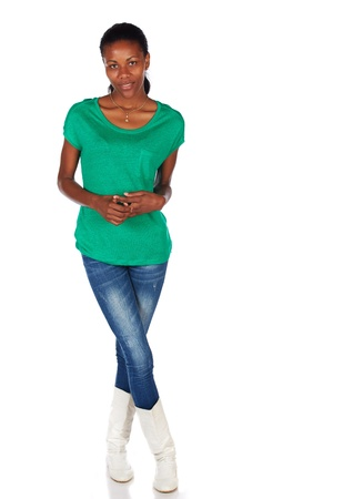 slicked back hair: Beautiful black african young adult woman casually dressed in an emerald green t-shirt and Blue jeans with white boots and with her hair slicked back into a ponytail and isolated on a white background