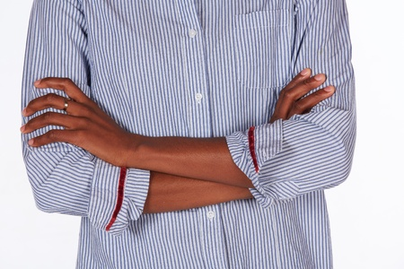 black african young adult businesswoman casually dressed in a blue pinstripe office shirt standing with crossed arms - body language Stock Photo - 19373045