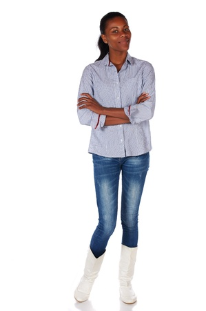 slicked back hair: Pretty black african young adult businesswoman casually dressed in a blue pinstripe office shirt, blue jeans, and white boots and with her hair slicked back into a ponytail and isolated on a white background Stock Photo
