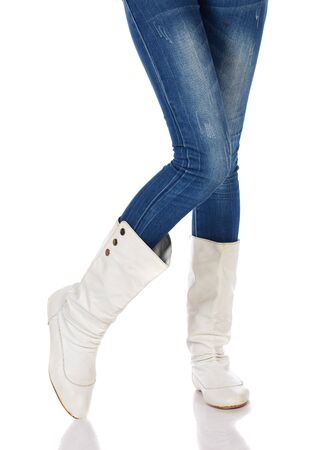 Legs and boots of a stylish and thin black african young adult woman casually dressed in blue jeans and white boots and isolated on a white background Stock Photo - 19371957
