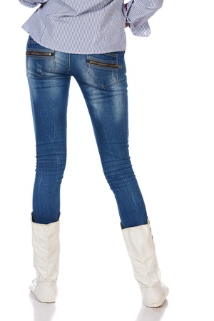 Legs and boots of a stylish and thin black african young adult woman casually dressed in blue jeans and white boots and isolated on a white background (from behind) Stock Photo - 19372830