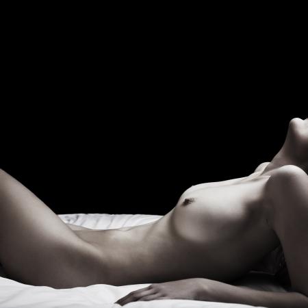 desnudo artistico: Bajo clave de imagen artística de una mujer adulta desnuda acostada sobre su espalda contra un fondo oscuro Foto de archivo