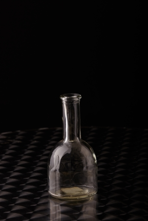 opaque: Empty glass bottle on a polished stainless steel table against a dark grey background