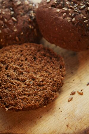 Dark rye bread on an old and worn wooden cutting board with copy space. Shallow DOF Stock Photo - 19372988