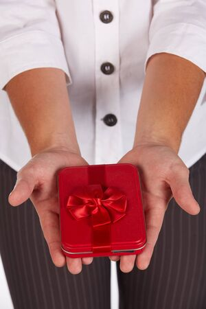 Female caucasian hands holding a red gift box with a red ribbon and bow Stock Photo - 19372661