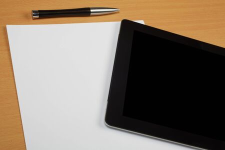 Paper, pen and tablet computer on wooden textured brown desk with copy space and clean paper to create own text.. Stock Photo - 19371675