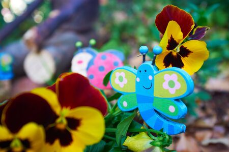 Wooden garden butterfly decoration between potted violets. Shallow Depth of Field - Focus on Butterfly Stock Photo - 19371958